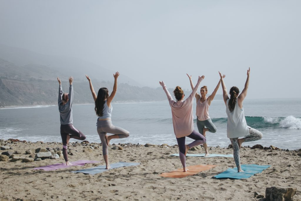 stock image group of women on beach doing yoga