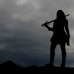 Goddess Warrior Training - Warrior standing atop mountain with sword drawn