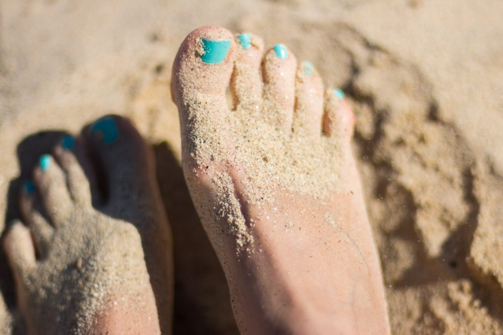 unsplash stock image toes in sand turquoise nails