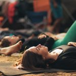 People laying on yoga mats supine. with one hand over heart, other hand on belly. Pranyama and meditation.